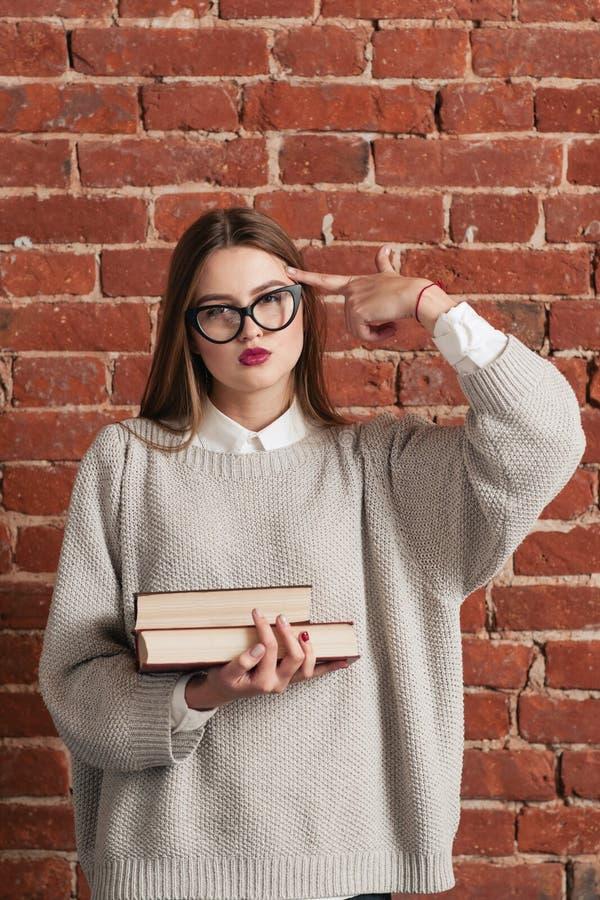 Estudante cansado com as mostras dos livros que disparam no gesto imagem de stock