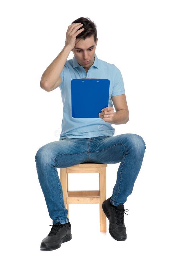 Estudante chocado que lê seu bloco de notas imagens de stock royalty free
