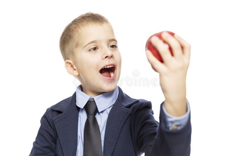A estudante com fome em um terno come uma maçã vermelha Close-up Isolado em um fundo branco imagens de stock royalty free