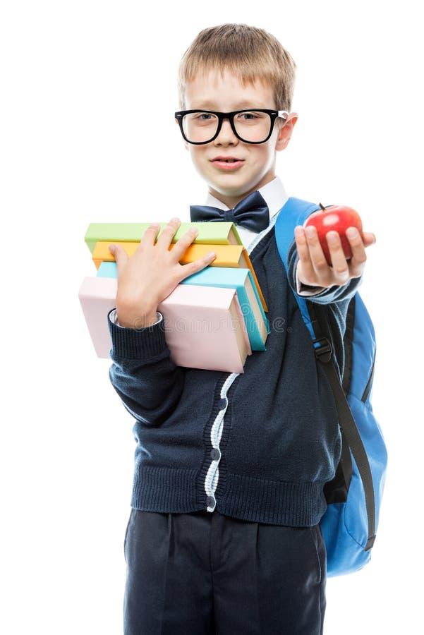 Estudante com livros e maçã que levanta no fundo branco dentro uni foto de stock