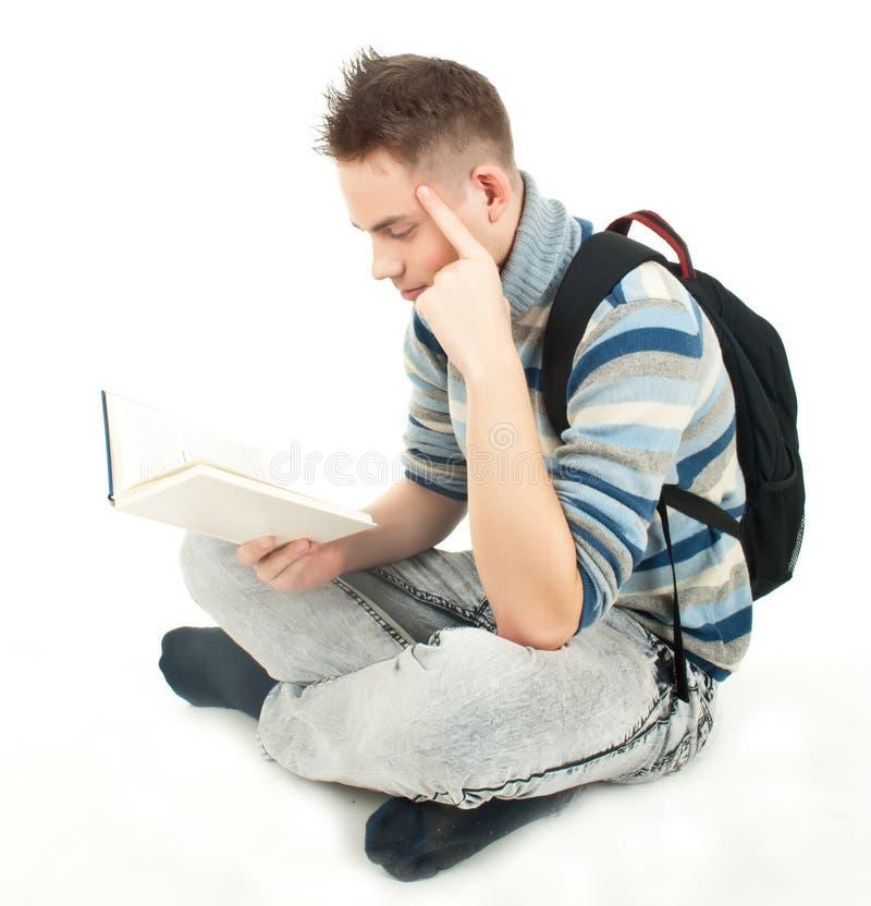 Estudante com o livro de leitura da trouxa imagem de stock royalty free