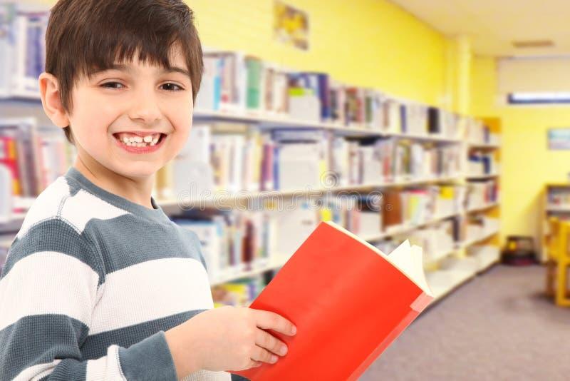 Estudante com o livro na biblioteca de escola imagens de stock royalty free