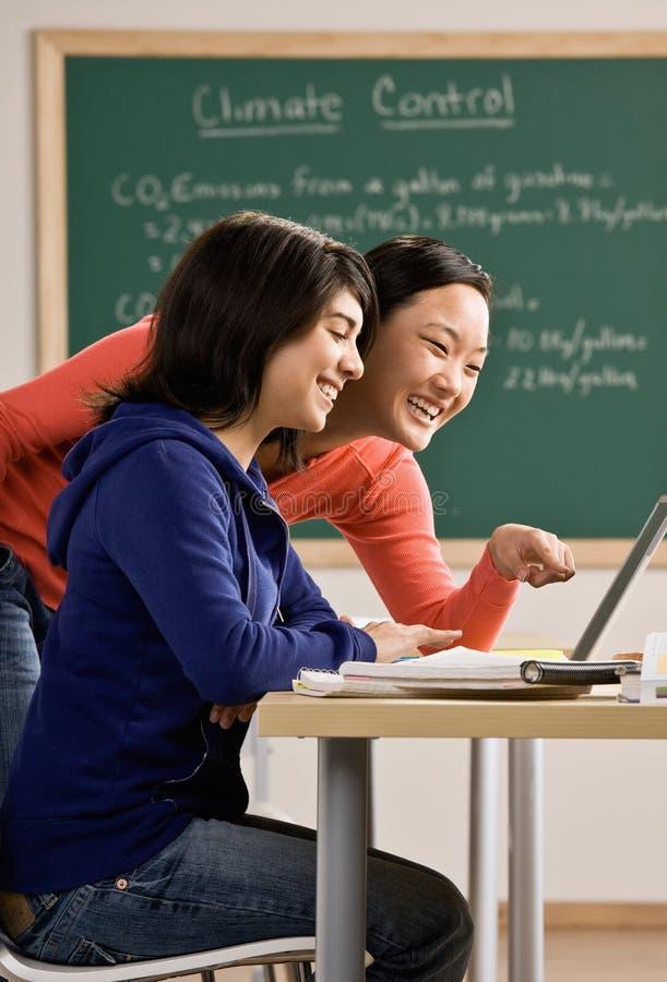 Estudante com o portátil que faz trabalhos de casa com amigo foto de stock royalty free