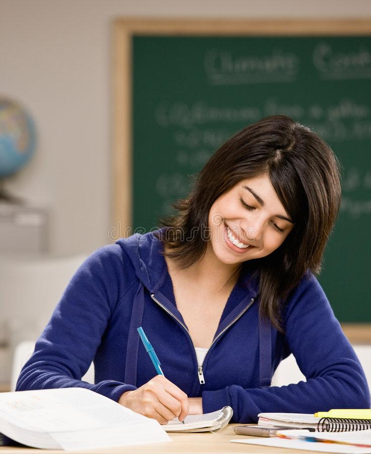 Estudante com os livros de texto que fazem trabalhos de casa fotografia de stock