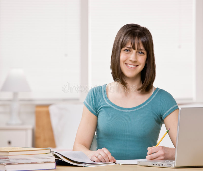 Estudante com os livros de texto que fazem trabalhos de casa fotografia de stock royalty free