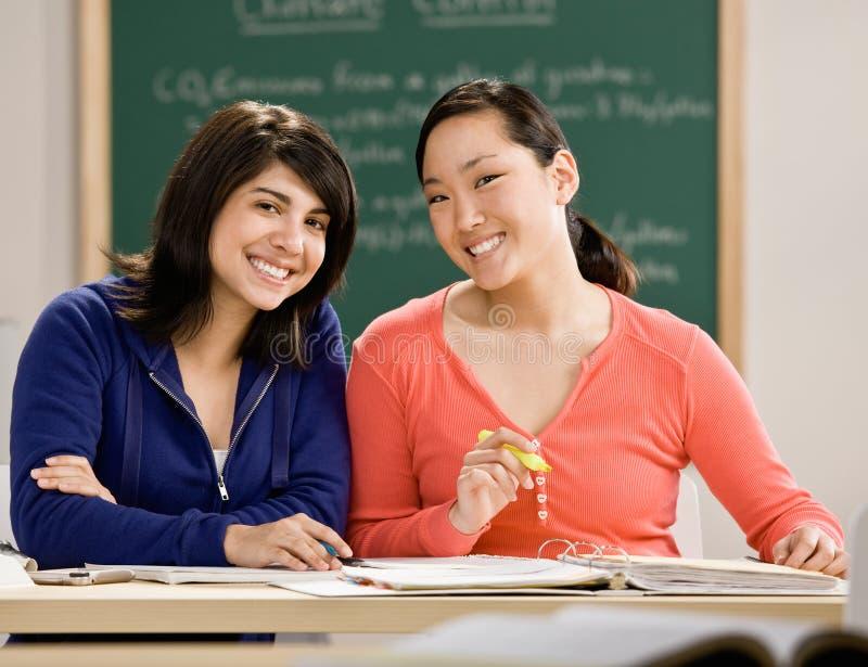 Estudante com os livros de texto que fazem trabalhos de casa com amigo imagem de stock royalty free