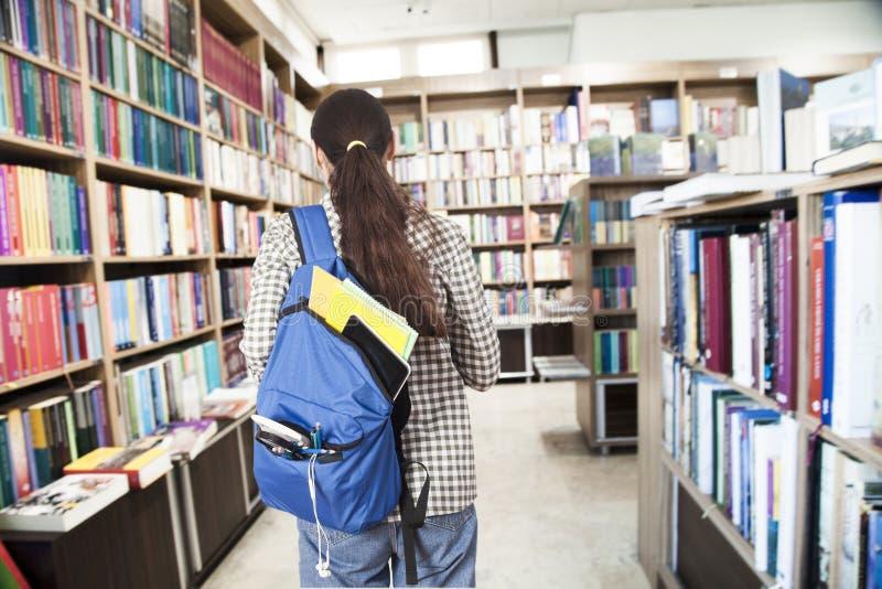 Estudante com a trouxa na biblioteca fotografia de stock royalty free
