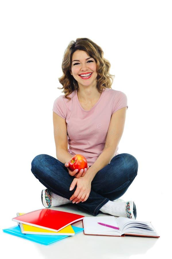Estudante consideravelmente fêmea dos jovens com a maçã vermelha isolada no branco imagens de stock
