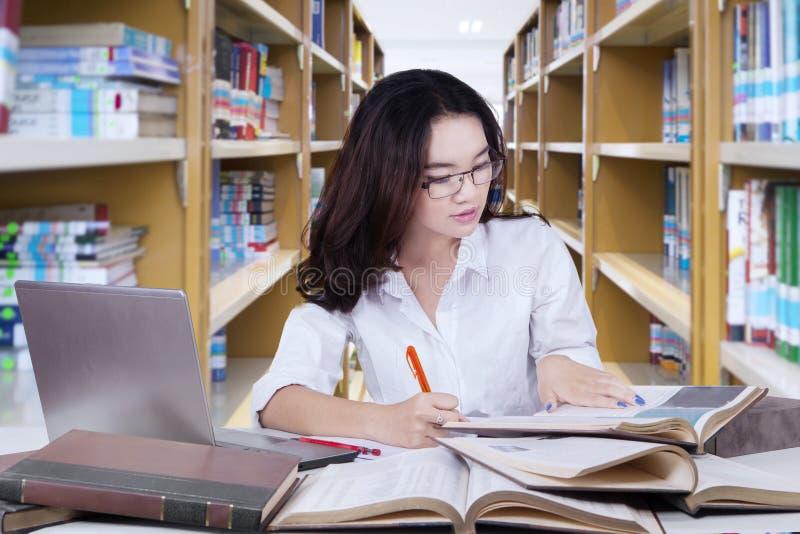 Estudante consideravelmente fêmea que faz o schoolwork na biblioteca fotografia de stock