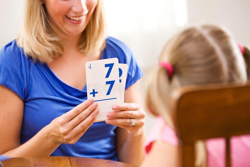 Estudante: A criança de ajuda da mãe aprende a matemática com cartões flash fotos de stock