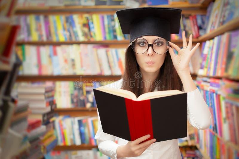 Estudante curioso Reading da escola um livro em uma biblioteca fotos de stock royalty free