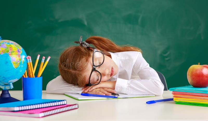 Estudante da estudante da criança cansado, adormecido sobre o quadro-negro da escola imagens de stock royalty free