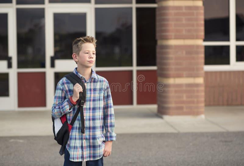 Estudante da escola primária ereto fora do prédio da escola fotos de stock