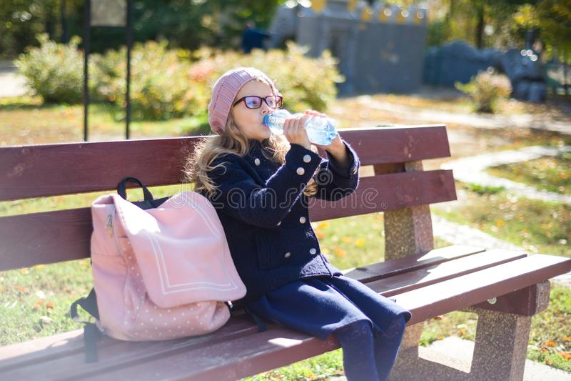 Estudante da escola primária da menina que senta-se no banco com trouxa, água potável da garrafa Parque da cidade do outono do fu imagem de stock