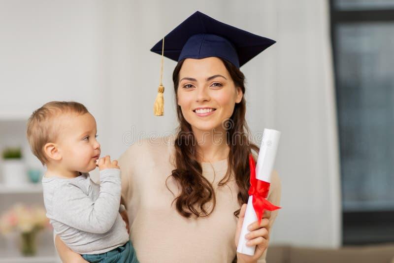 Estudante da mãe com bebê e diploma em casa fotos de stock royalty free