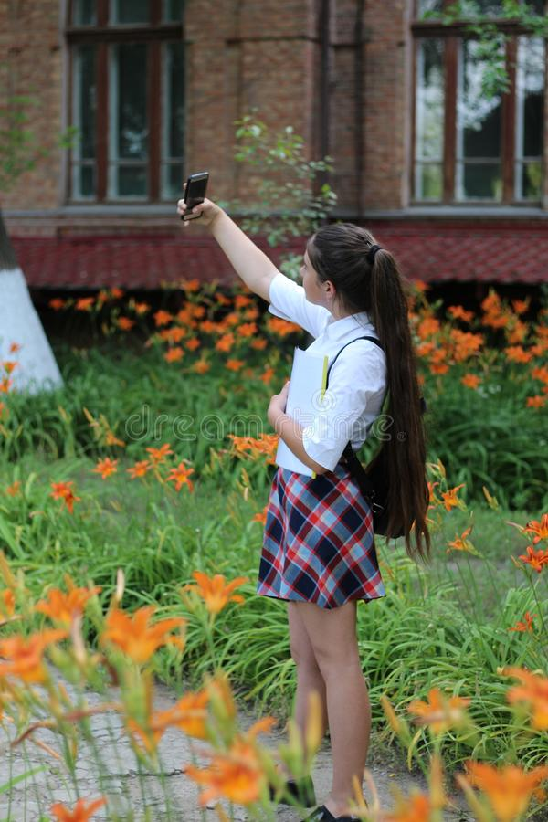 A estudante da menina com cabelo longo na farda da escola faz o selfie foto de stock