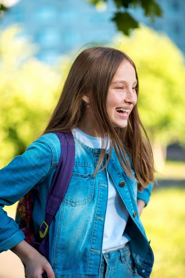 Estudante da menina verão na natureza No revestimento da sarja de Nimes atrás de uma trouxa Retornos de sorriso felizes em casa R imagem de stock