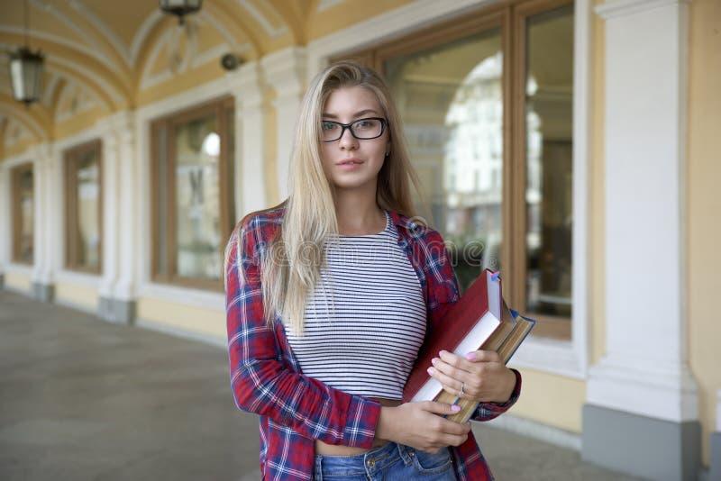 Estudante da moça com os vidros e o cabelo longo, vestidos em um plai imagens de stock royalty free
