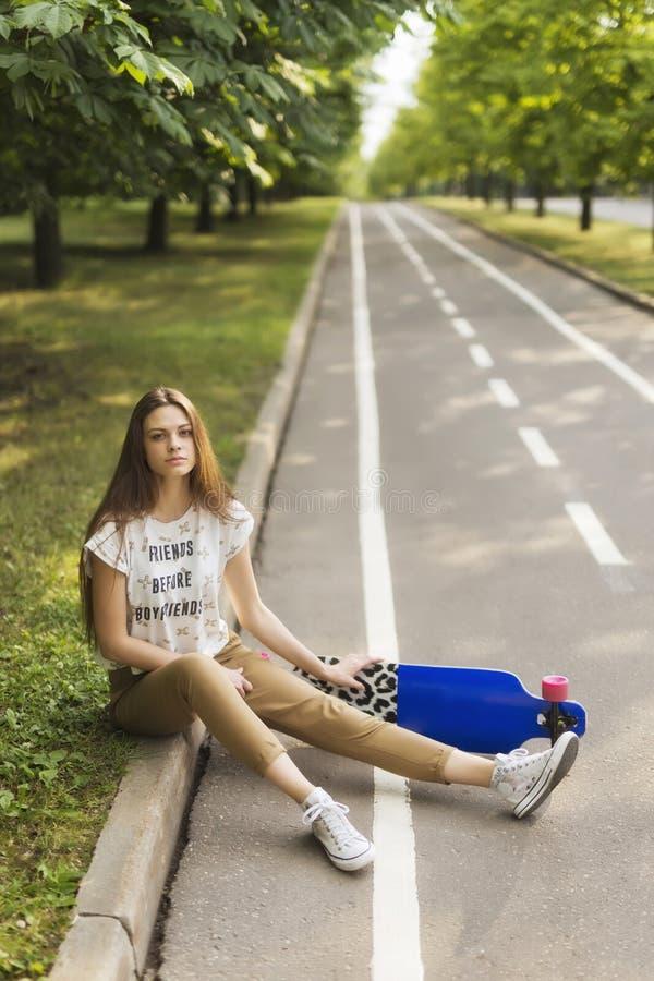 Estudante da moça em uma camisa e na calças que sentam-se em um tapete no parque, ao lado do longboard skateboarding outdoors foto de stock