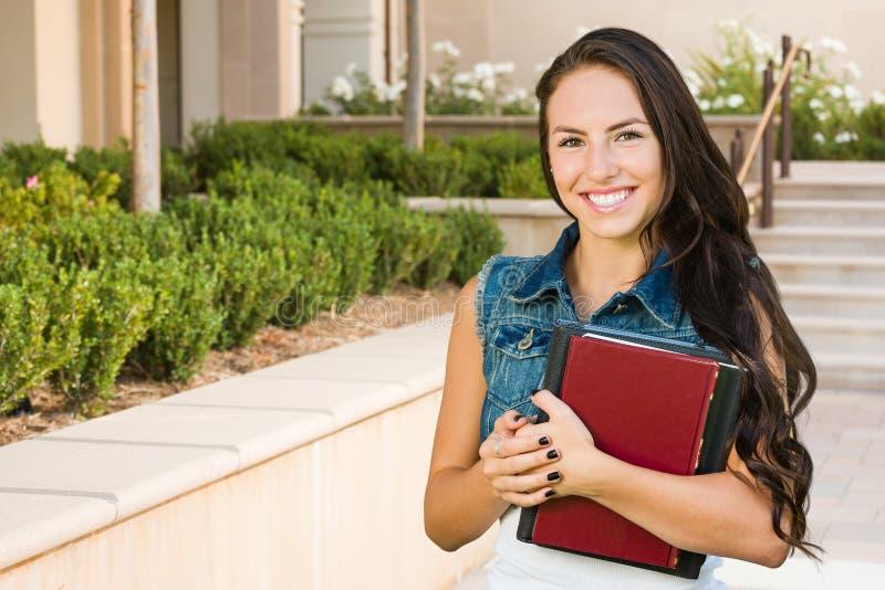 Estudante da moça da raça misturada com os livros de escola no terreno fotos de stock