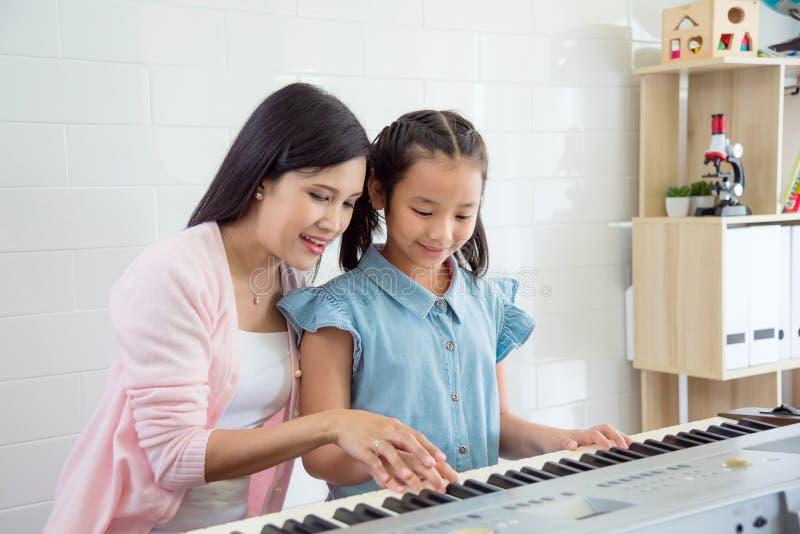 Estudante de ensino do professor para jogar o teclado na escola fotografia de stock royalty free