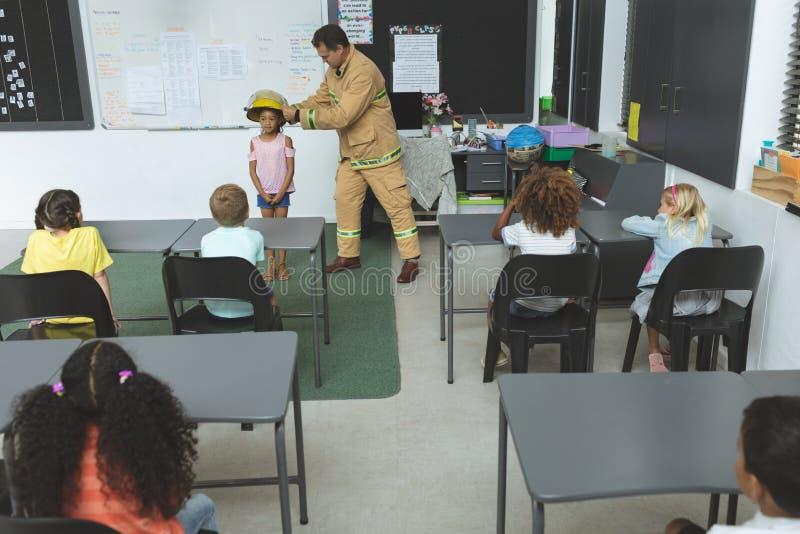 Estudante de ensino do sapador-bombeiro sobre a proteção contra incêndios na sala de aula fotos de stock