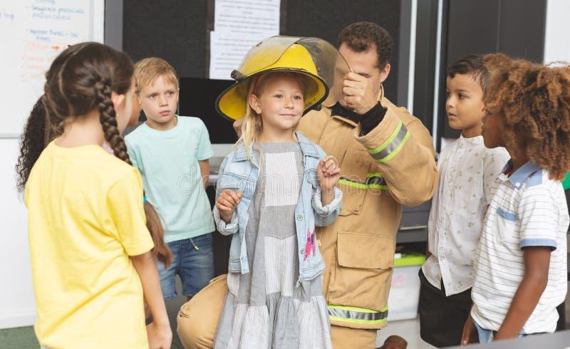 Estudante de ensino do sapador-bombeiro sobre a proteção contra incêndios na sala de aula imagens de stock