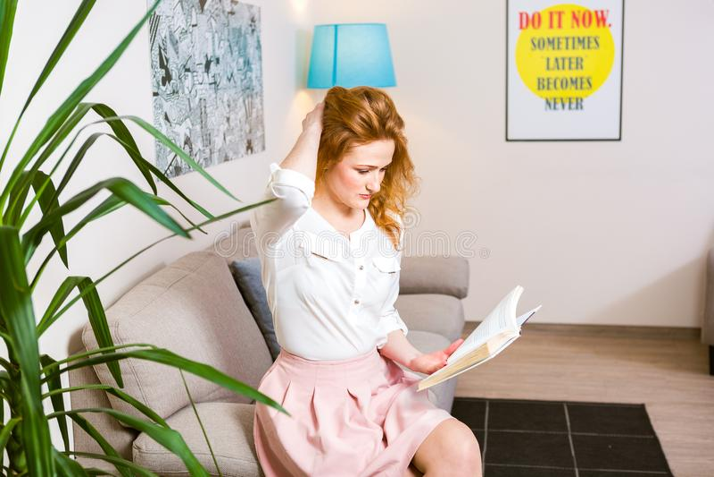 Estudante de jovem mulher bonito com cabelo vermelho longo no livro de leitura cor-de-rosa da saia e da camisa, livro de texto di fotografia de stock royalty free