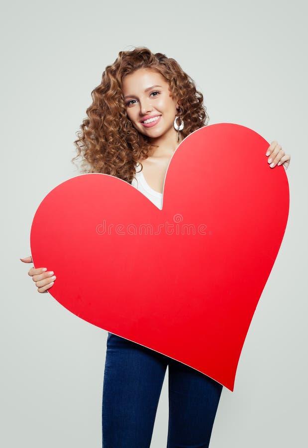 Estudante de jovem mulher com fundo de papel vazio vermelho do coração com espaço da cópia para anunciar o mercado ou a colocação imagens de stock