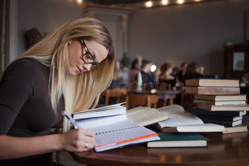 Estudante de jovem mulher da universidade Preparando o exame e a aprendizagem da biblioteca das lições em público foto de stock royalty free