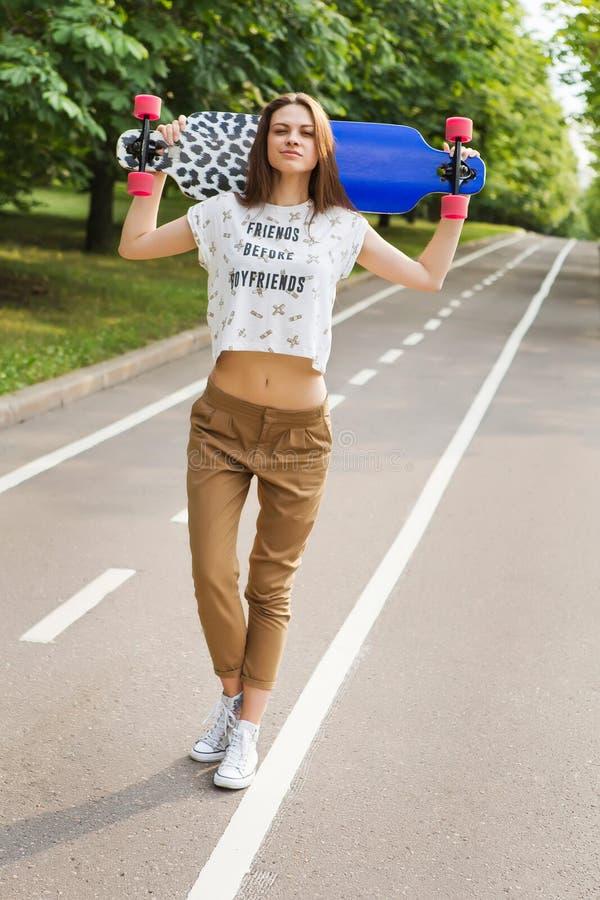 Estudante de jovem mulher na moda que está em um parque e que guarda seu lorgbord principal skateboarding lifestyle fotografia de stock