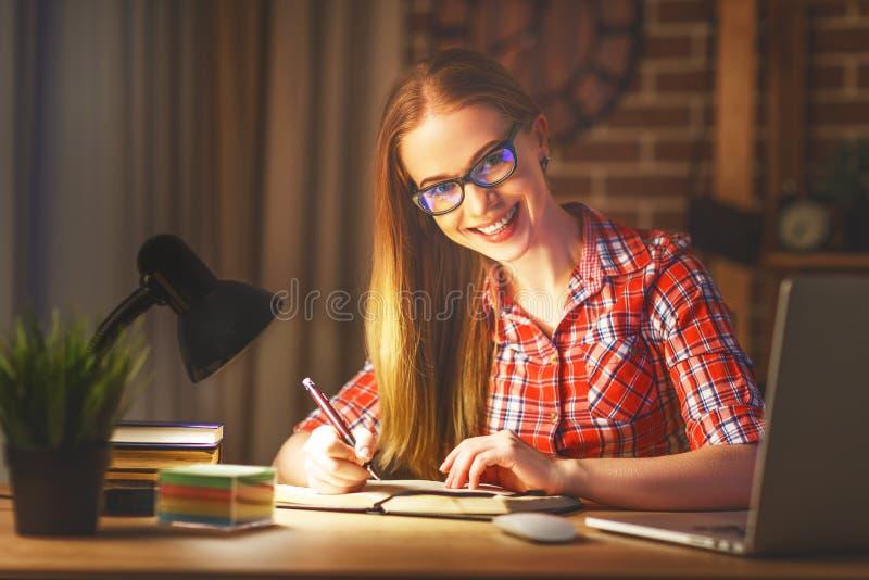Estudante de jovem mulher que trabalha no computador na noite foto de stock