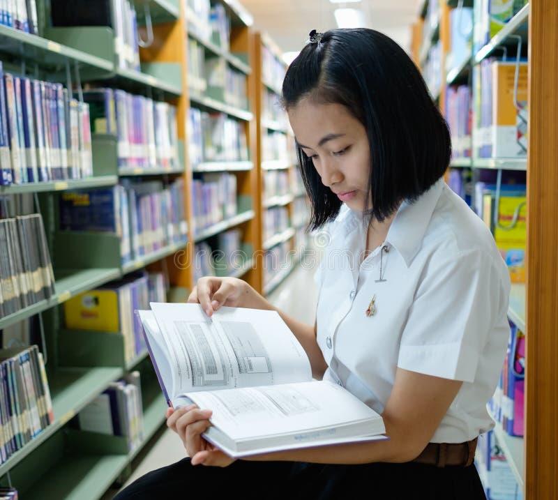 Estudante de jovem mulher tailandês que lê um livro fotos de stock royalty free
