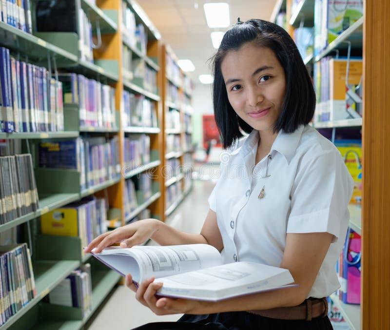 Estudante de jovem mulher tailandês que lê um livro fotos de stock
