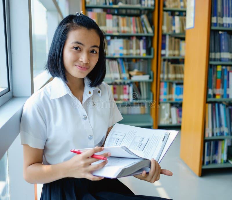 Estudante de jovem mulher tailandês que lê um livro imagem de stock
