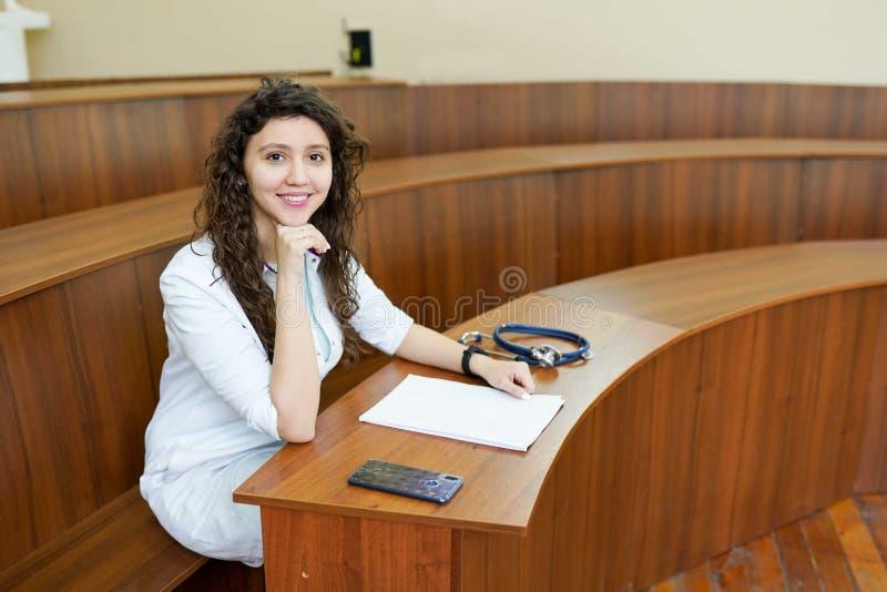 Estudante de Medicina com o estetosc?pio e o telefone que olham a c?mera, tiro na classe Doutor f?mea imagens de stock