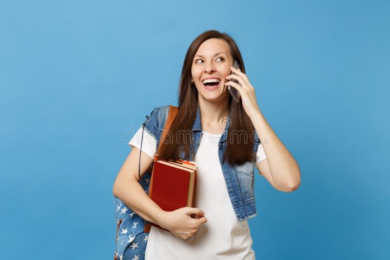 Estudante de mulher alegre novo com os livros de escola da posse da trouxa que fala no telefone celular que conduz a conversação  fotos de stock