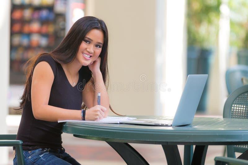 Estudante de mulher asiático novo de Smilling que senta-se na tabela que trabalha com fotografia de stock royalty free