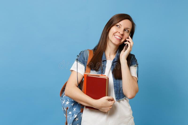 Estudante de mulher bonito novo com a trouxa que guarda livros de escola que fala no telefone celular que conduz a conversação ag imagem de stock