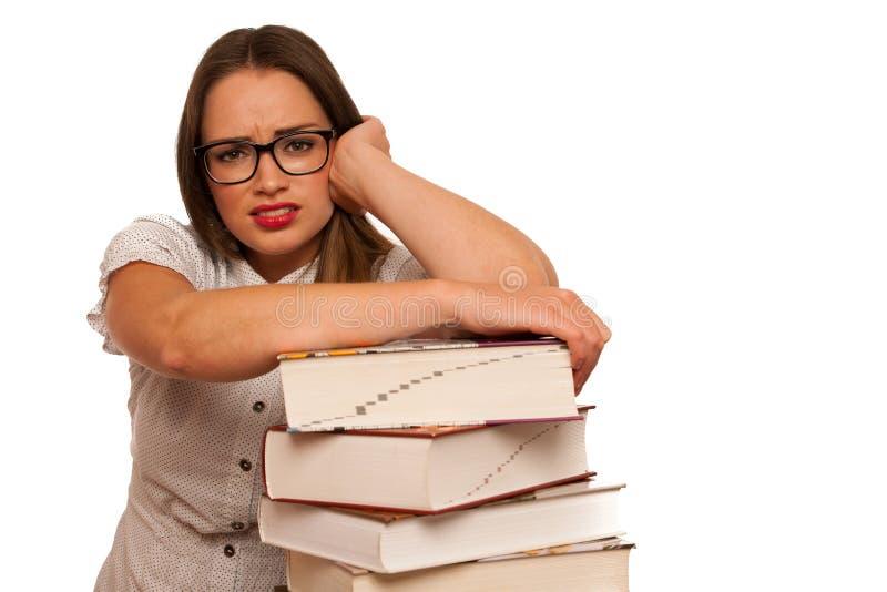 Estudante de mulher caucasiano asiático forçado que aprende nas toneladas de livros fotos de stock royalty free
