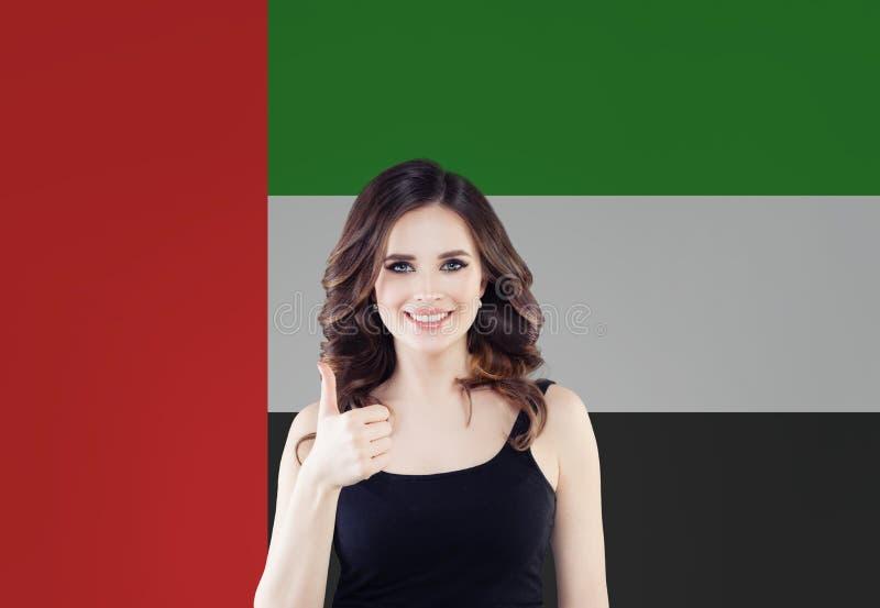 Estudante de mulher feliz com polegar acima no fundo da bandeira dos UAE Emiratos Árabes Unidos, curso e para aprender o conceito imagens de stock royalty free