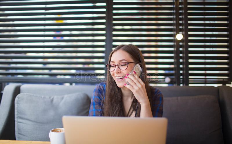 Estudante de mulher feliz que tem a conversação telefônica da pilha após o trabalho no rede-livro portátil foto de stock