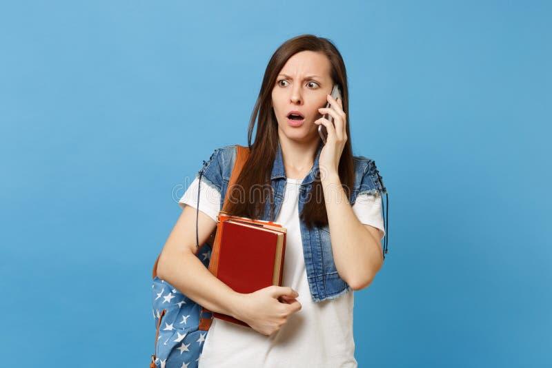 Estudante de mulher interessado novo com a trouxa que guarda livros de escola que fala no telefone celular, conversação de conduç fotografia de stock royalty free