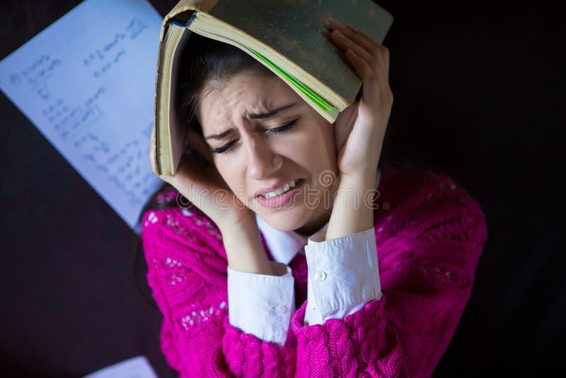Estudante de mulher moreno de vista engraçado que tenta estudar em sua sala Processo engraçado de estudo para exames imagem de stock