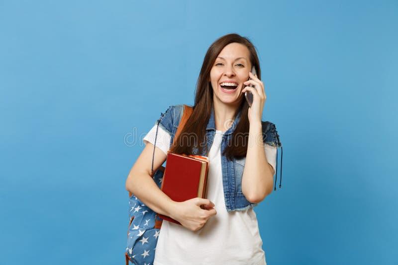 Estudante de mulher de riso novo com os livros de escola da posse da trouxa que fala no telefone celular que conduz a conversação imagens de stock