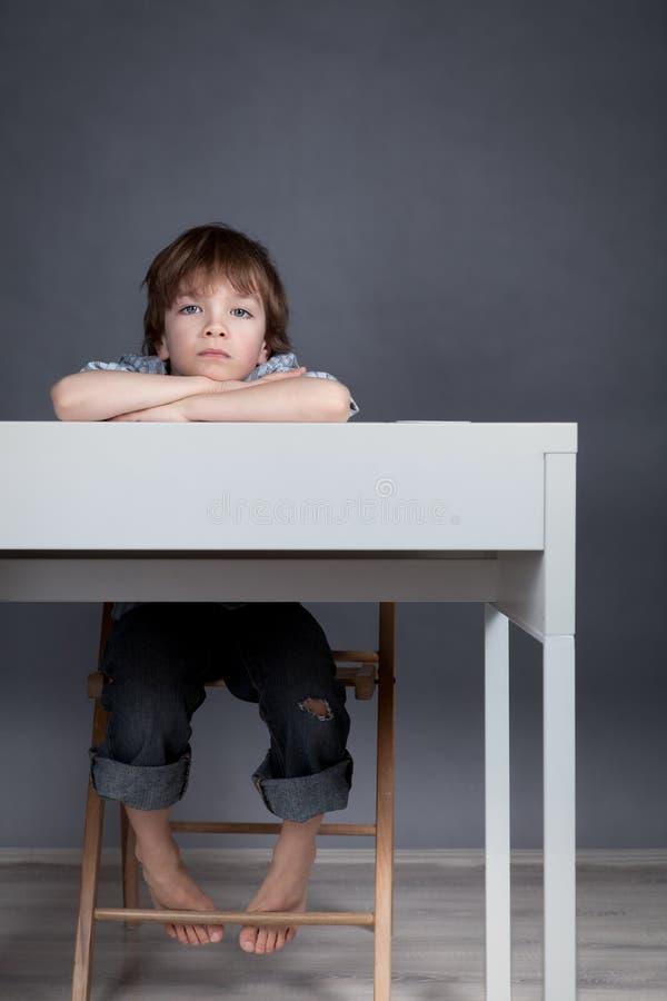 Estudante de pensamento que senta-se na mesa fotografia de stock