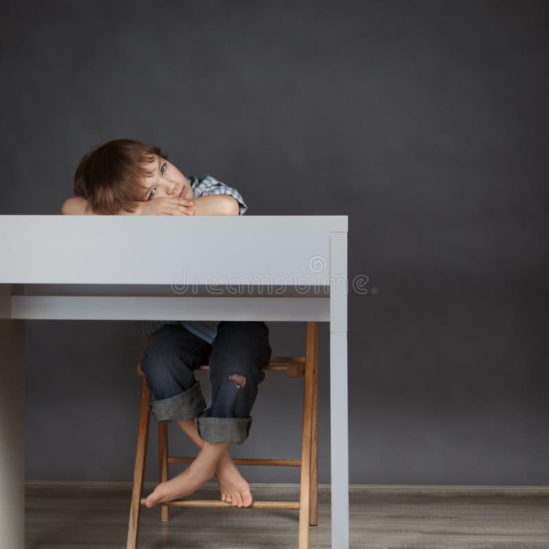 Estudante de pensamento que senta-se na mesa fotos de stock