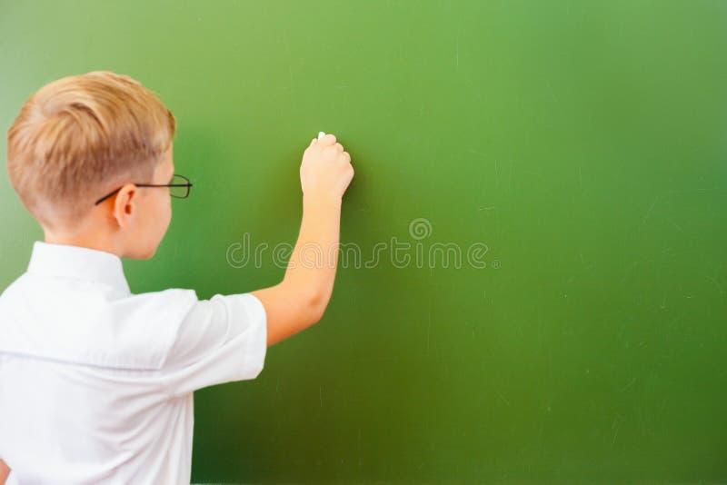 A estudante de primeiro grau escreveu no quadro-negro com giz na sala de aula fotografia de stock