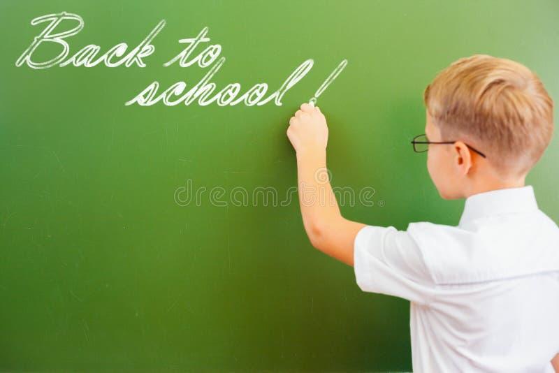 A estudante de primeiro grau escreveu no quadro-negro com giz na sala de aula imagens de stock royalty free
