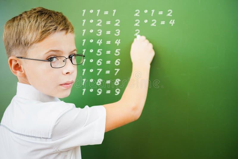 A estudante de primeiro grau escreveu a tabela de multiplicação no quadro-negro foto de stock